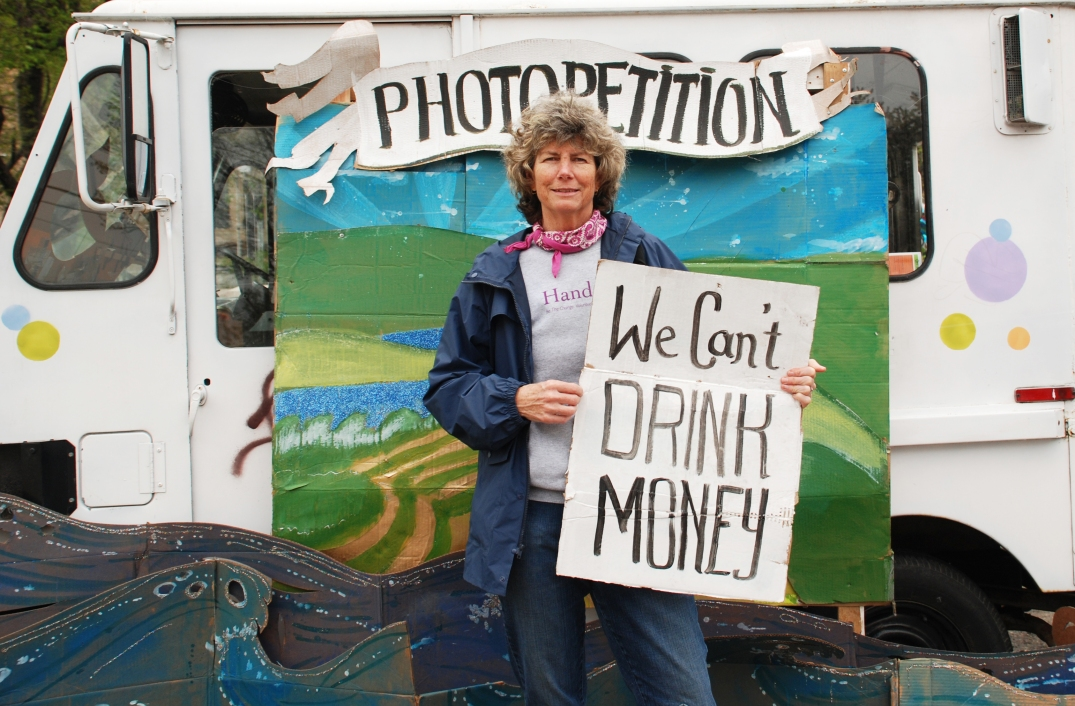 A woman holding a sign that says We Can't Drink Money, in front of a landscape backdrop.
